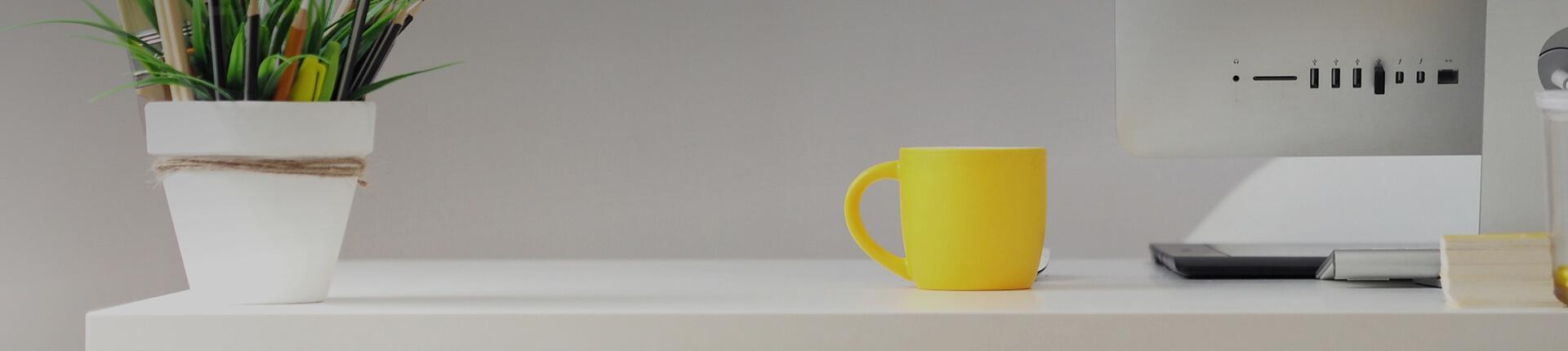 Pflanze, Tasse und Mac auf Schreibtisch
